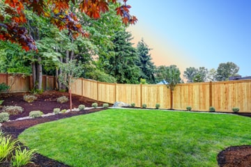 Fenced in yard with perfectly green and healthy lawn.